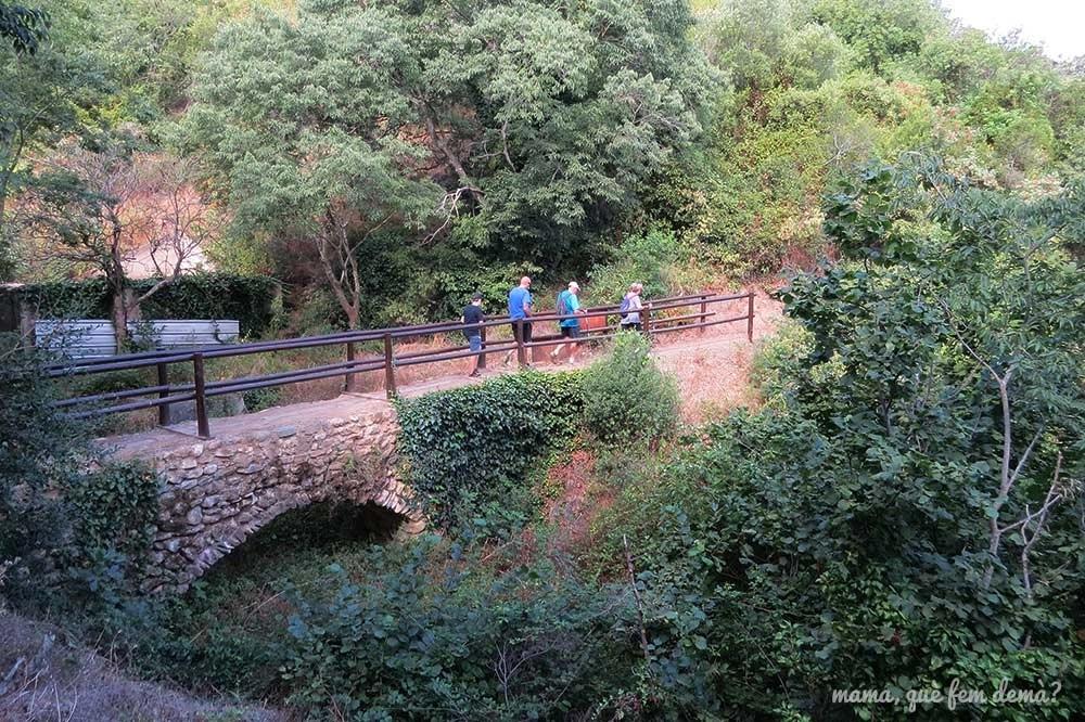 Gente cruzando un puente medieval del Camí del Rec de la Selva del Camp