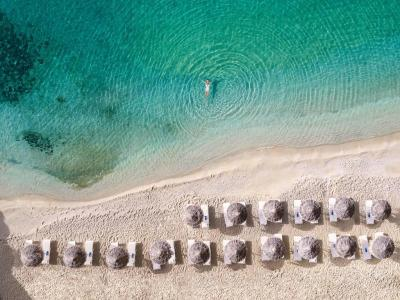 Mykonos Blu, Grecotel Exclusive Resort Mykonos - Grecia e In esclusiva per Mamatours 4 Notti Sistemazione Water-front Bungalow Partenza Agosto a partire da euro2530 per personasoggiorno minimo 5 notti e Include - Prima colazione - Cesto di frutta e acqua minerale in camera allrsquoarrivo - Wi-fi gratuito e La Struttura This property is 5 minutes walk from the beach Mykonos Blu, Grecotel Exclusive Resort boasts a spa, a 2-level infinity pool and luxurious sea-view accommodation It stands on its private part of Psarou beach, offering free beach sun beds e Accommodation at Mykonos Blu consists of sophisticated bungalows and villas, with built-in bathtubs or phototherapy showers Some units have private pools, indoor or outdoor hot tubs BO LCD TVs, DVDCD players and free Wi-Fi are standard e A state-of-the-art fitness room, sauna and beauty salon are available at the resortrsquos Elixir Fitness Gallery Spa Guests can also find a jewellery shop and the largest conference centre in Cyclades e Aegean Poets serves a la carte lunch and dinner with seafood specialities Poolside lunches and drinks are available at the LrsquoArchipel brasserie Delos Lounge Bar is ideal for an after-dinner drink e Mykonos Airport is 4 km from the resort The town of Mykonos is a 5-minute drive away The hotel can also arrange for sunset champagne sailing or helicopter tours