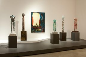 Installation shot of sculptures and a painting at a museum