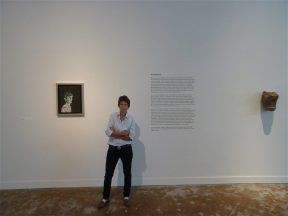Installation shot of an artist standing with her self portrait