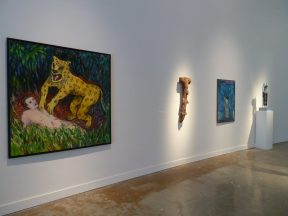 Installation shot of sculptures and paintings at a museum