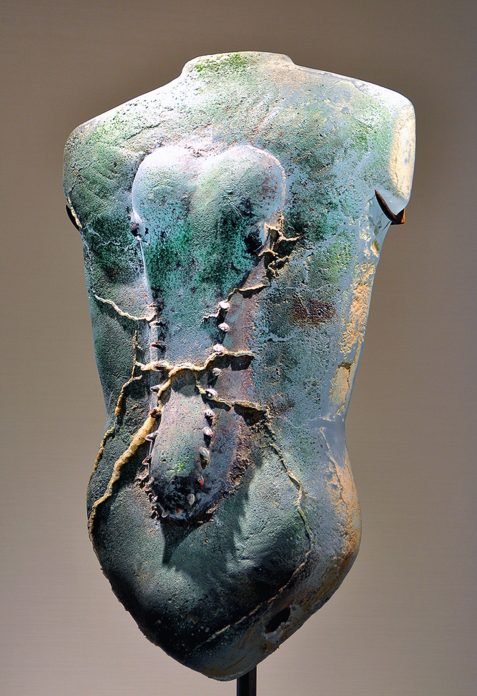 A glass sculpture shaped like a human torso with a raised crocodile head shape in the middle