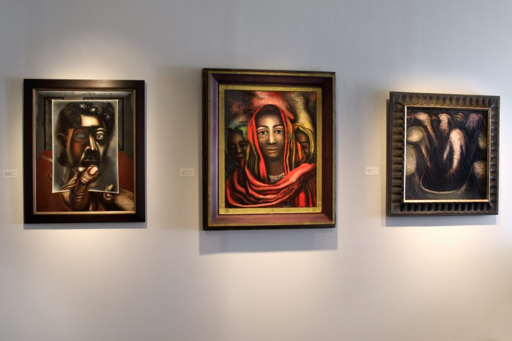Installation shot of three paintings by David Alfaro Siqueiros