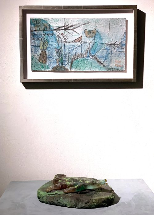 Installation shot of a small glass crocodile beneath a painting
