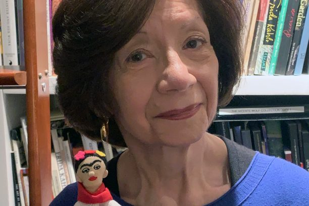 A photograph of a woman standing in front of bookshelves wearing a bright blue sweater and holding a small Frida Kahlo doll