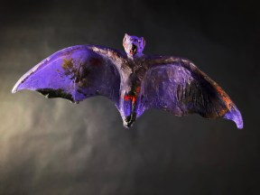 A glass sculpture suspended in midair of a purple bat with its wings outstretched