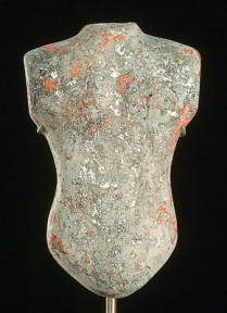 Grey glass sculpture of a torso with flecks of white and red
