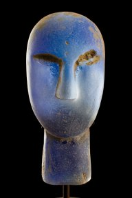 Blue glass sculpture of a large, primitive looking head