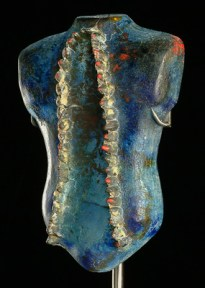 Glass sculpture of a blue torso with two lines of protruding teeth down the front