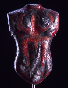 Black and red glass sculpture of a torso with a crest design