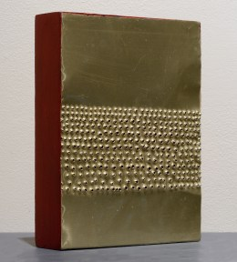 A small wood and metal sculpture. with a pattern of nail holes in the thin gold metal.