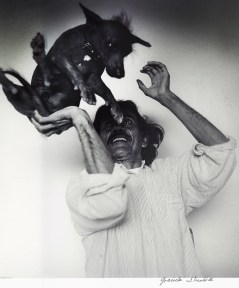 A photograph of a man wearing a white shirt playfully throwing a hairless dog in the air