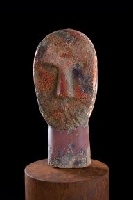 Brown glass sculpture shaped like a primitive head