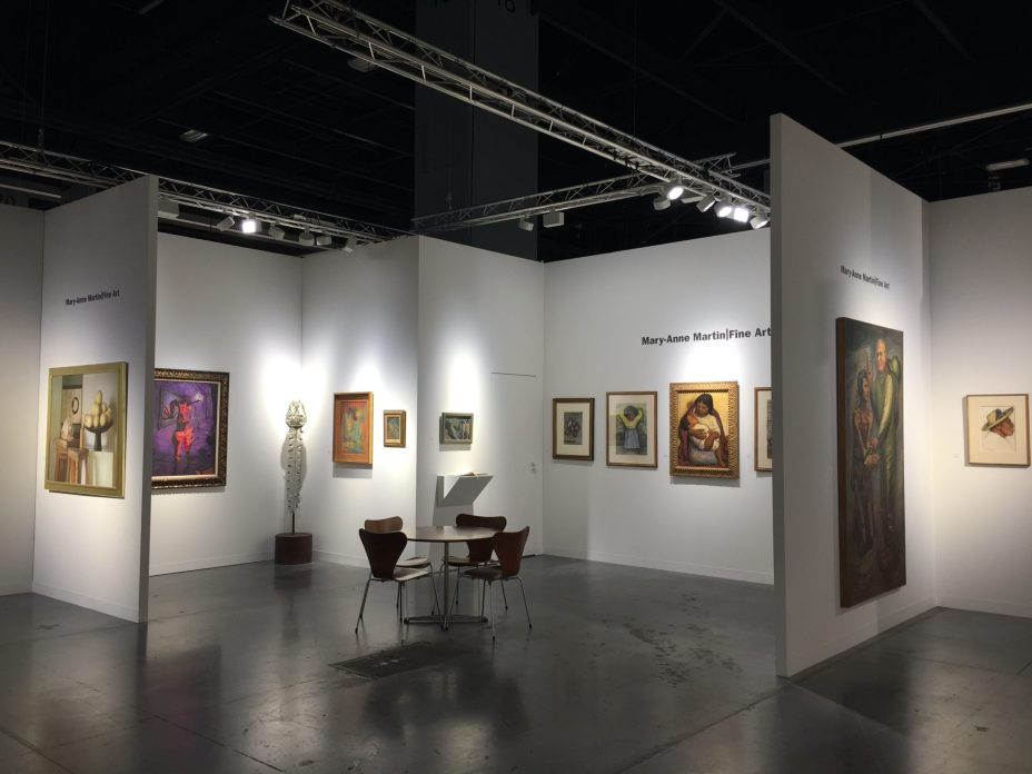 Installation shot of a booth at an art fair with paintings and sculptures
