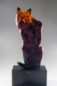 A glass sculpture of a red and orange cat with black spots. It sits facing the viewer with its tail curled around its legs.