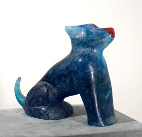 A blue glass sculpture of a seated dog with a red nose
