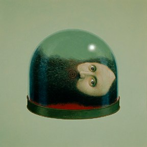 The head of a man with long hair and a beard is encased by a bell jar.
