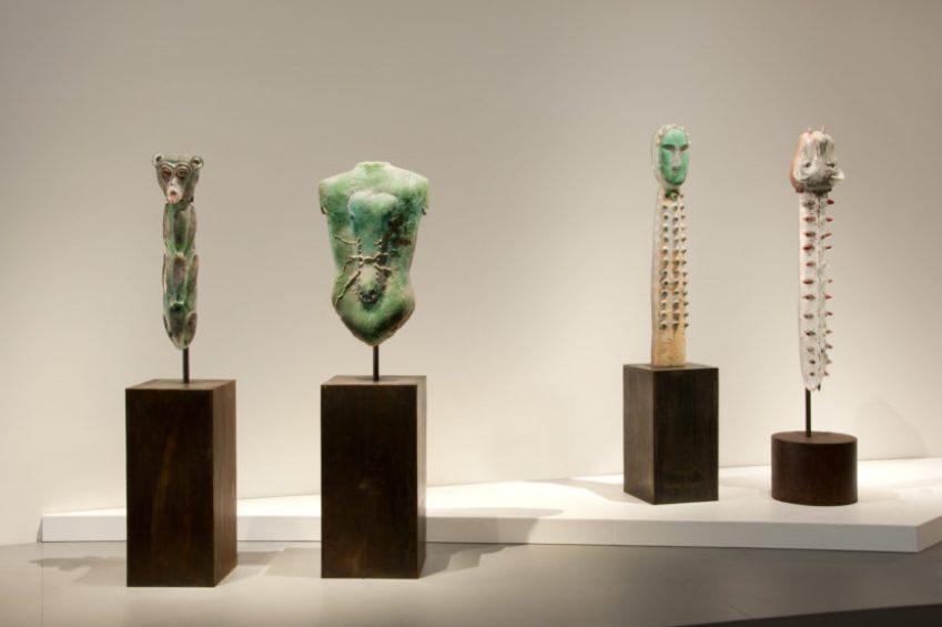 Installation shot of four large, vertical glass sculptures on metal pedestals