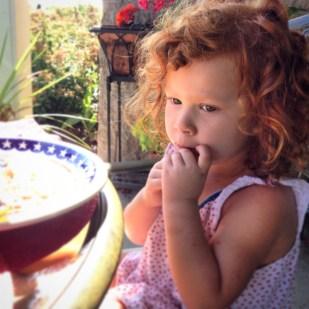 Cristina desayuna en la pequeña mesa de jardín que tienen Ellen y Bruce en su patio frente al Lago Michigan.