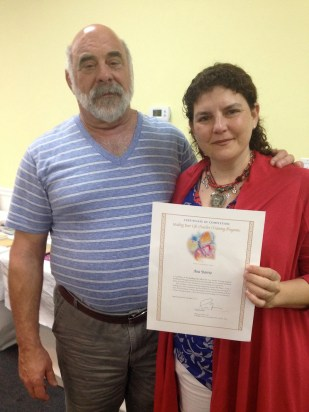 Ana se certificó como instructora. Aquí con Paul Ferrini mostrando su diploma.