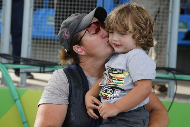 Kimberly Rhode of the United States kisses her son Carter after winning the bronze medal in the women's skeet bronze medal match at Olympic Shooting Center at the 2016 Summer Olympics in Rio de Janeiro, Brazil, Friday, Aug. 12, 2016. (AP Photo/Hassan Ammar)