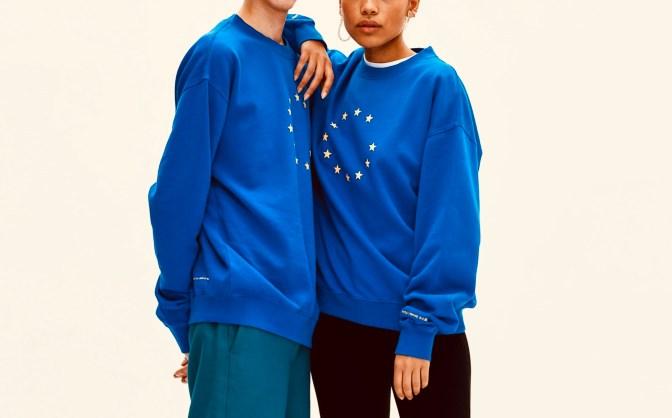 Zwei nebeneinanderstehende Menschen tragen jererils den blauen EUNIFY Sweater mit der EU Fahne