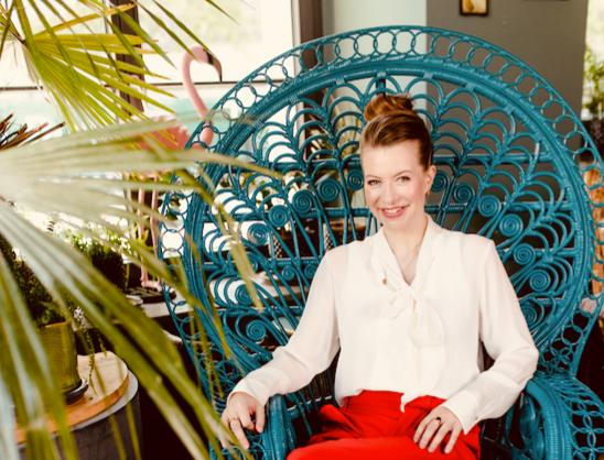 Die Autorin von Mami und Gör sitzt auf einem türlisen Korbstuhl. Sie trägt eine weiße Bluse. Vor ihr das Grün einer Palme.