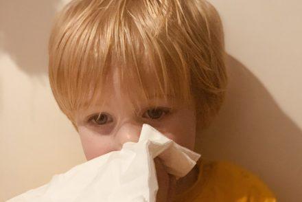 Ein zwei Jahre altes Kind, erkältet mit einem Papiertaschentuch vor der Nase