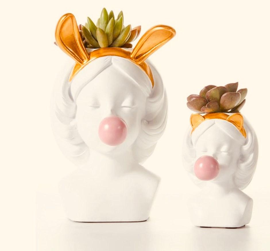 Zwei Vasen in form von Mädchen-Köpfen. Beide Kaugummi-Mädchen-Vasen kauen auf einem Kaugummi und machen eine Blase