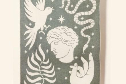 Mythologie-Decke. Konterfei eines griechischen Gottes, Schlange, Zweig, Hand und Vogel in cremeweiß auf einer dunkelgrünen Wolldecke.