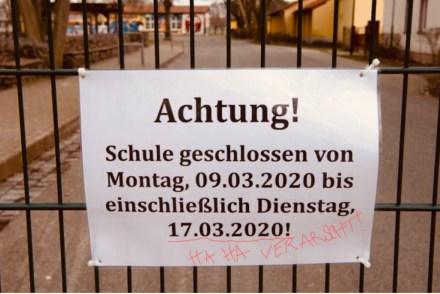 Schild an Schulzaun mit der Angabe der Schulöffnung am 17. März. Darunter in roter Handschrift haha, verarscht...