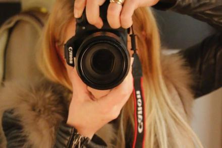 Blonde Frau mit Spiegelreflexkamera. Julie von Gold a