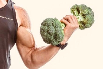 Starker Muskelmann trainiert Bizeps mit Brokkolihantel