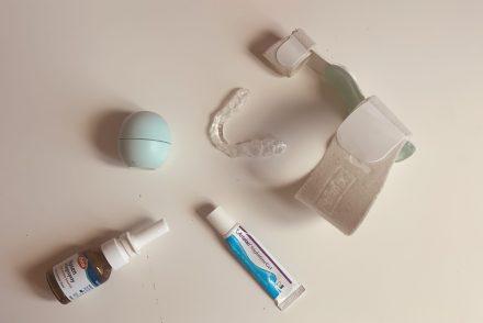 Auf dem Tisch liegen eine Beißschiene, ein Zehentrenner, eine Nasenöl, Augensalbe und Lippencremal als Sinnbild für nächtliche Notwendikeiten im Alter.