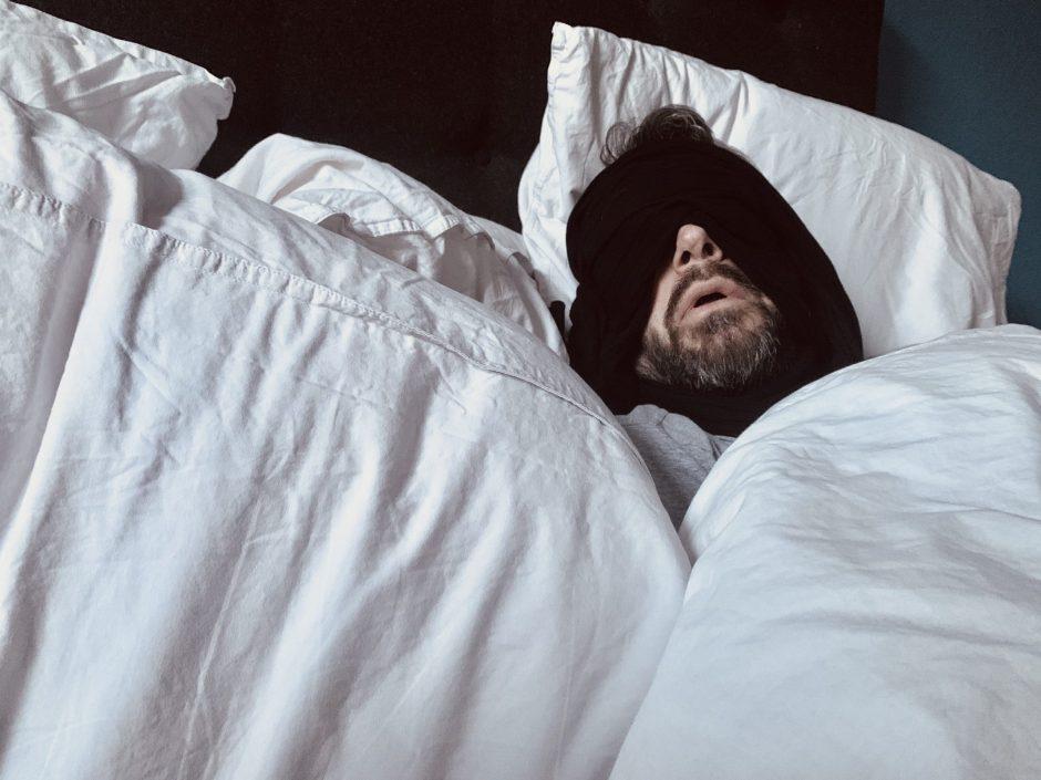 Der Mann liegt mit halbabgedecktem Gesicht im Bett und leidet nach seiner AstraZeneca Impfung.