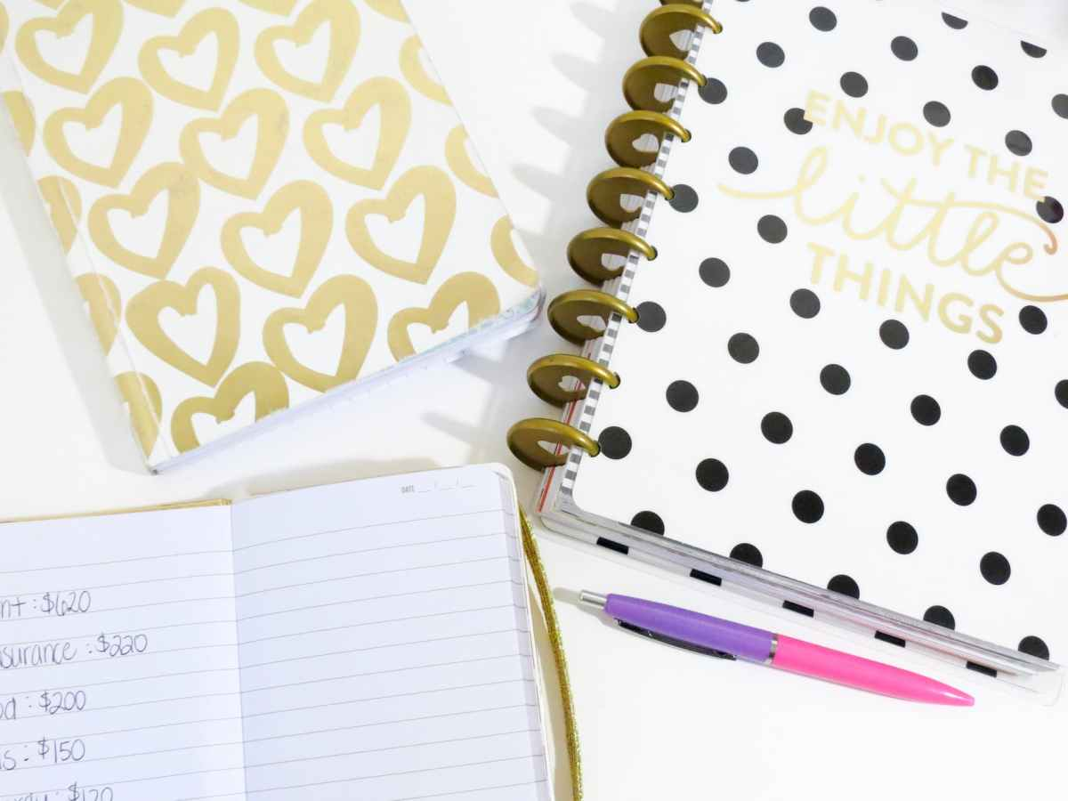 opened notebook beside pink and purple pen and white and black polka dot notebook