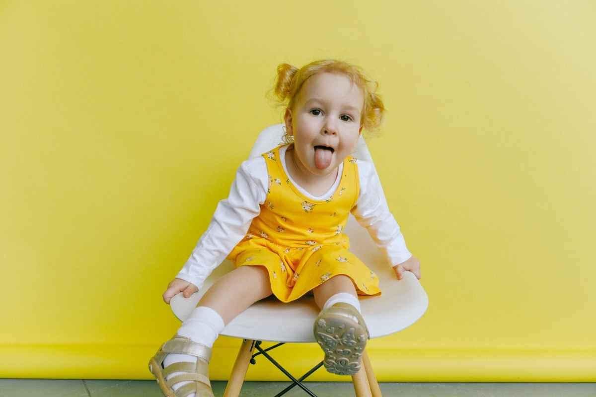 girl in white and yellow long sleeve dress doing funny face