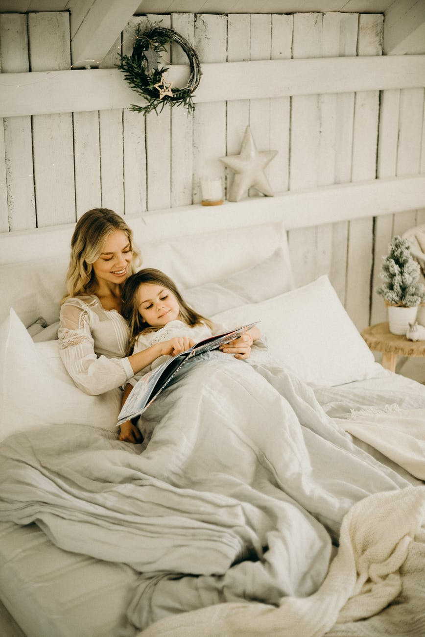 woman and girl lying in bed while holding book