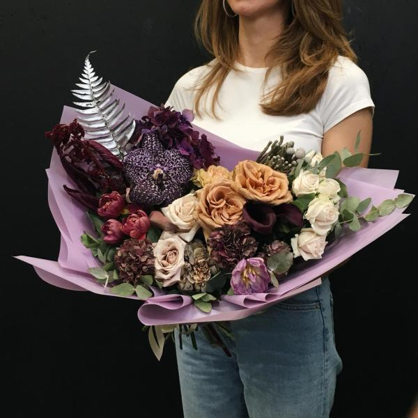 A statement art piece wrapped in paper! This bouquet is made from a mix of premium large Roses in a variety of colors, cut stems of Orchid, Hydrangeas, Tulips, Brunia, Amaranthus and black Calla Lilly.