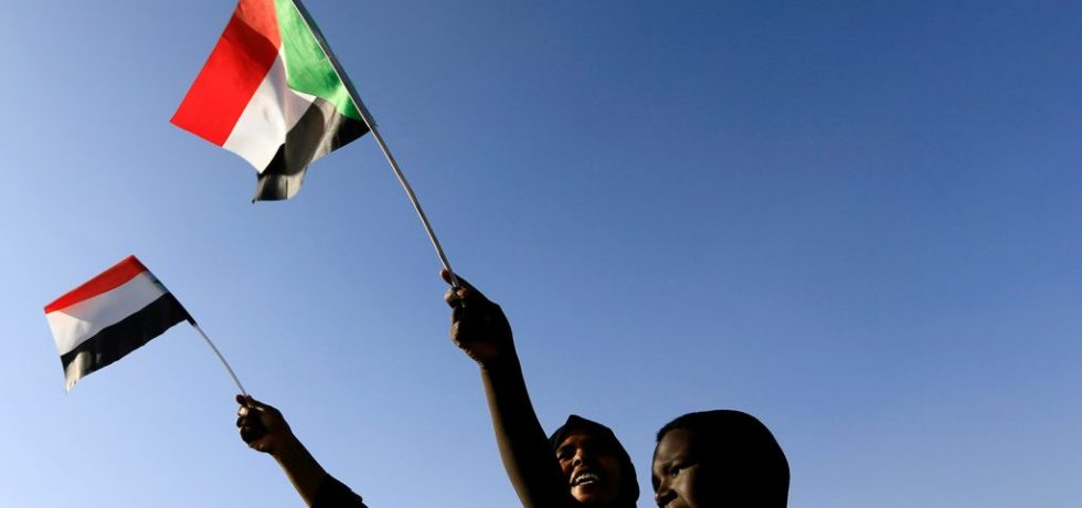 Sudanese waving national flag.