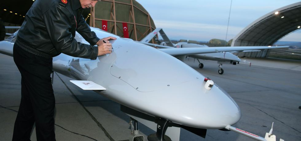 Turkish President, Erdogan, signs a drone at a military base.