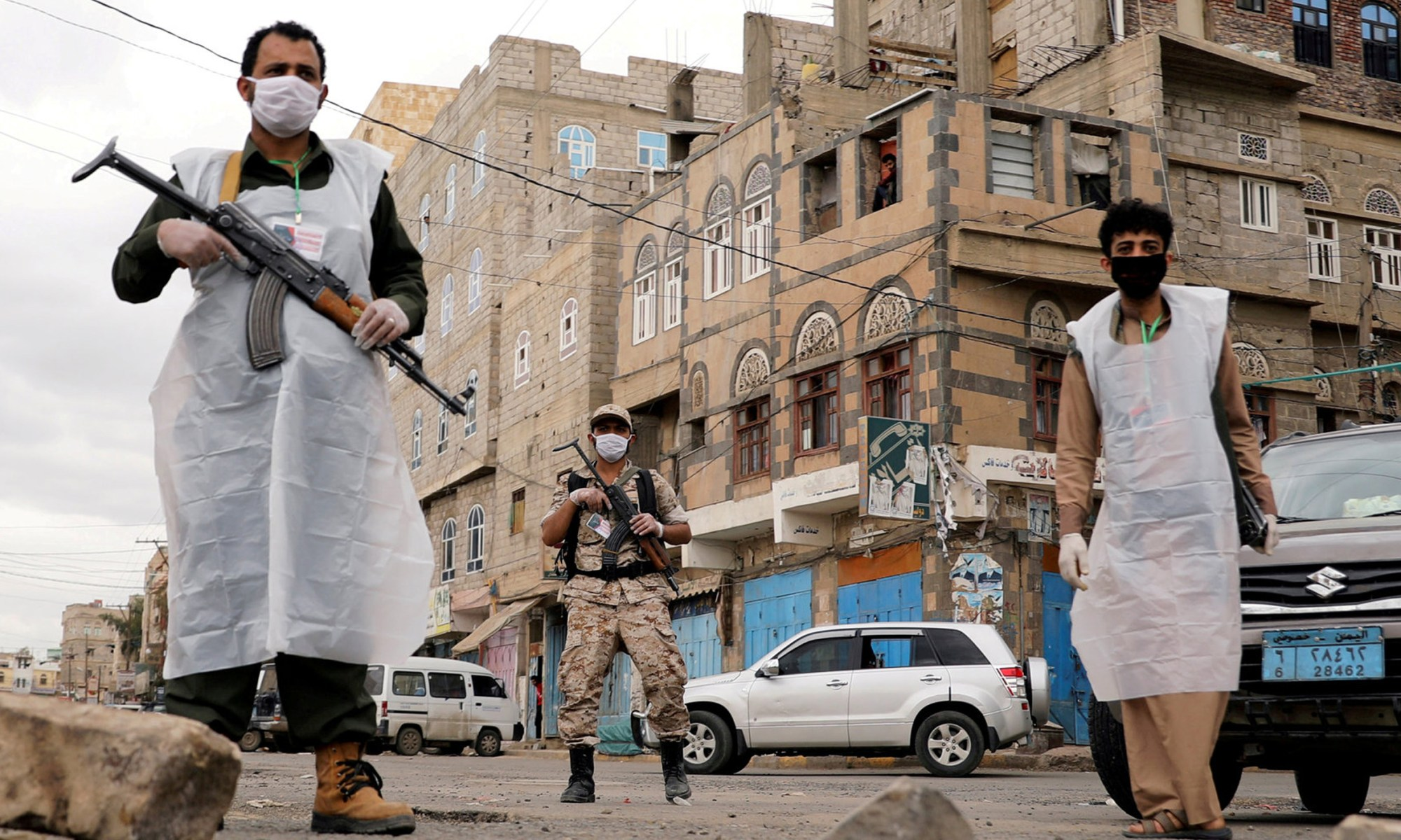 Men standing in masks with gun in hands on Yemeni street.