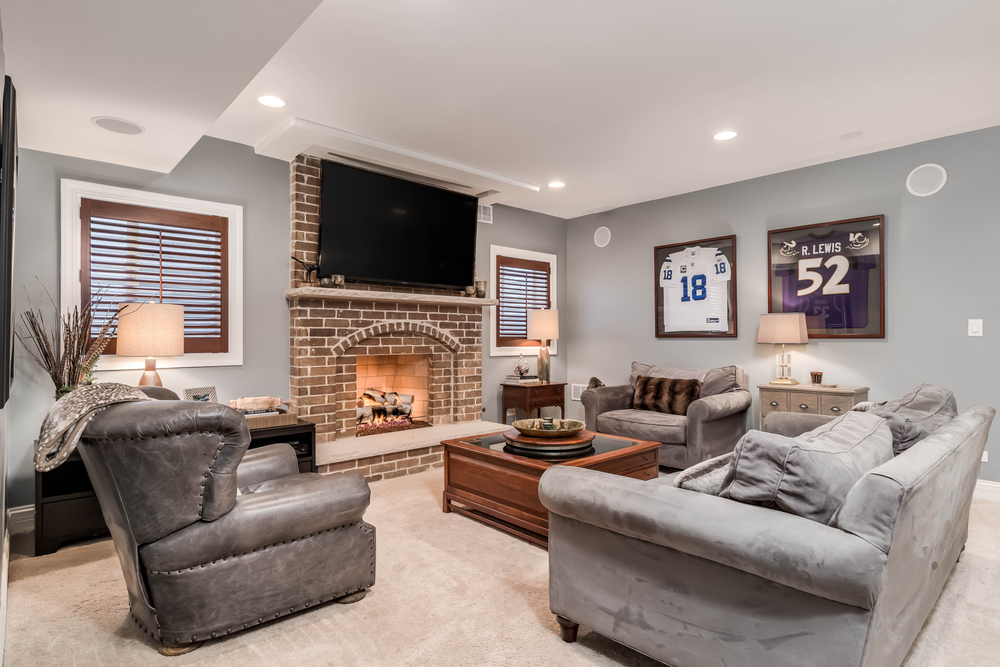 man cave living room with television mounted above a lit fireplace