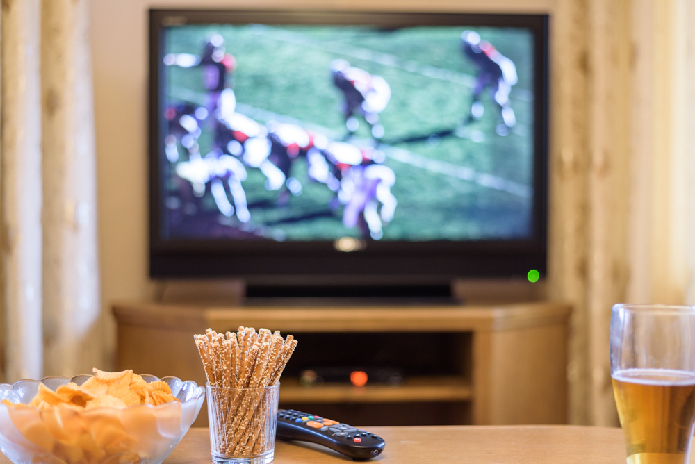 watching football match on television with snacks and alcohol