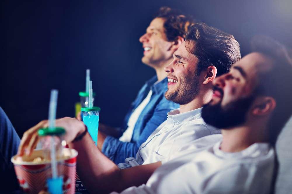 group of happy friends watching movie in cinema
