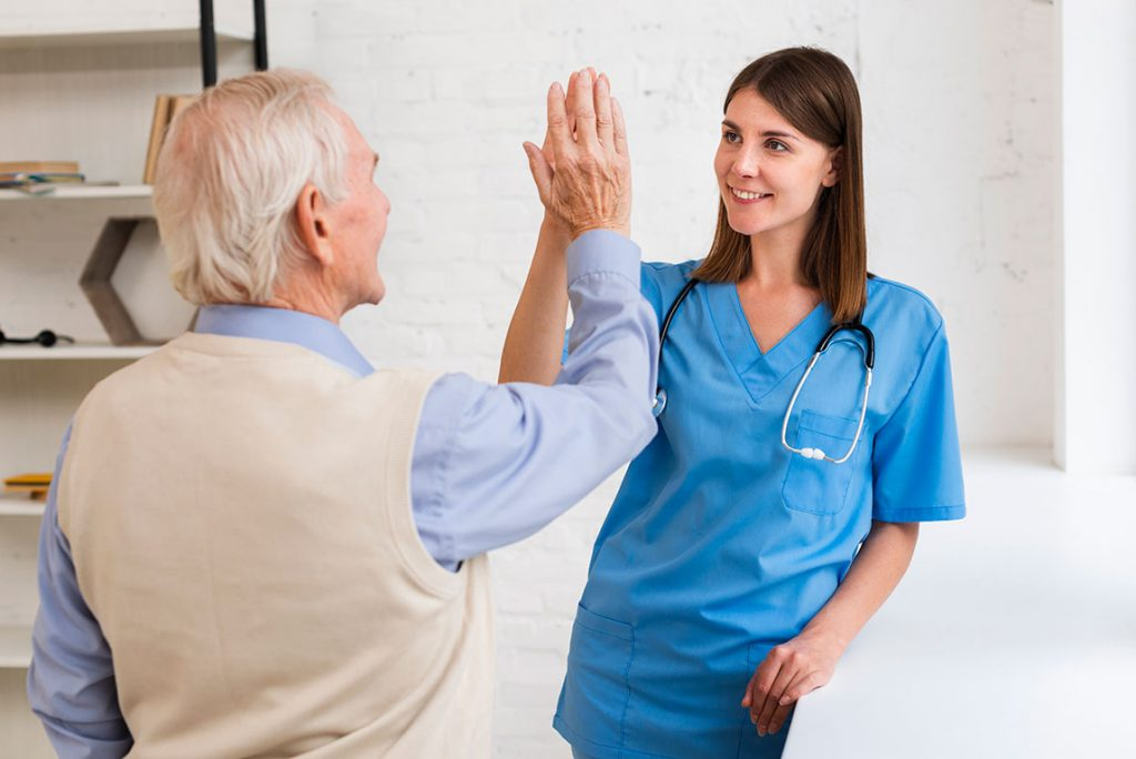caregiver high fiving with old man