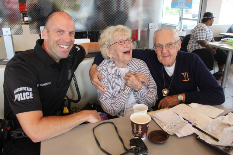 Manchester Police Officer Paul Rondeau shares coffee and a laugh with Marge Bienvenue and Howard McCarthy.