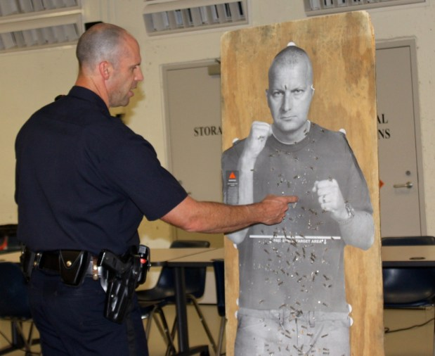 "Officer Paul Rondeau talks about target practice using a cardboard ""target man"" cutout."