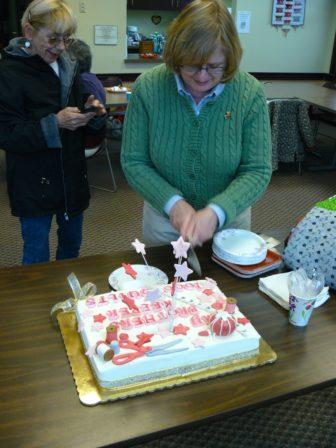 My Brother's Keeper founder Linda Heminway cuts the celebratory cake.