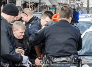 A police officer handcuffs Lovensky Jonick Maschabaz-Mesidor on Thursday.